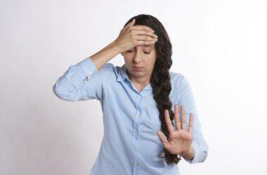 Kobieta trzymająca się za głowę