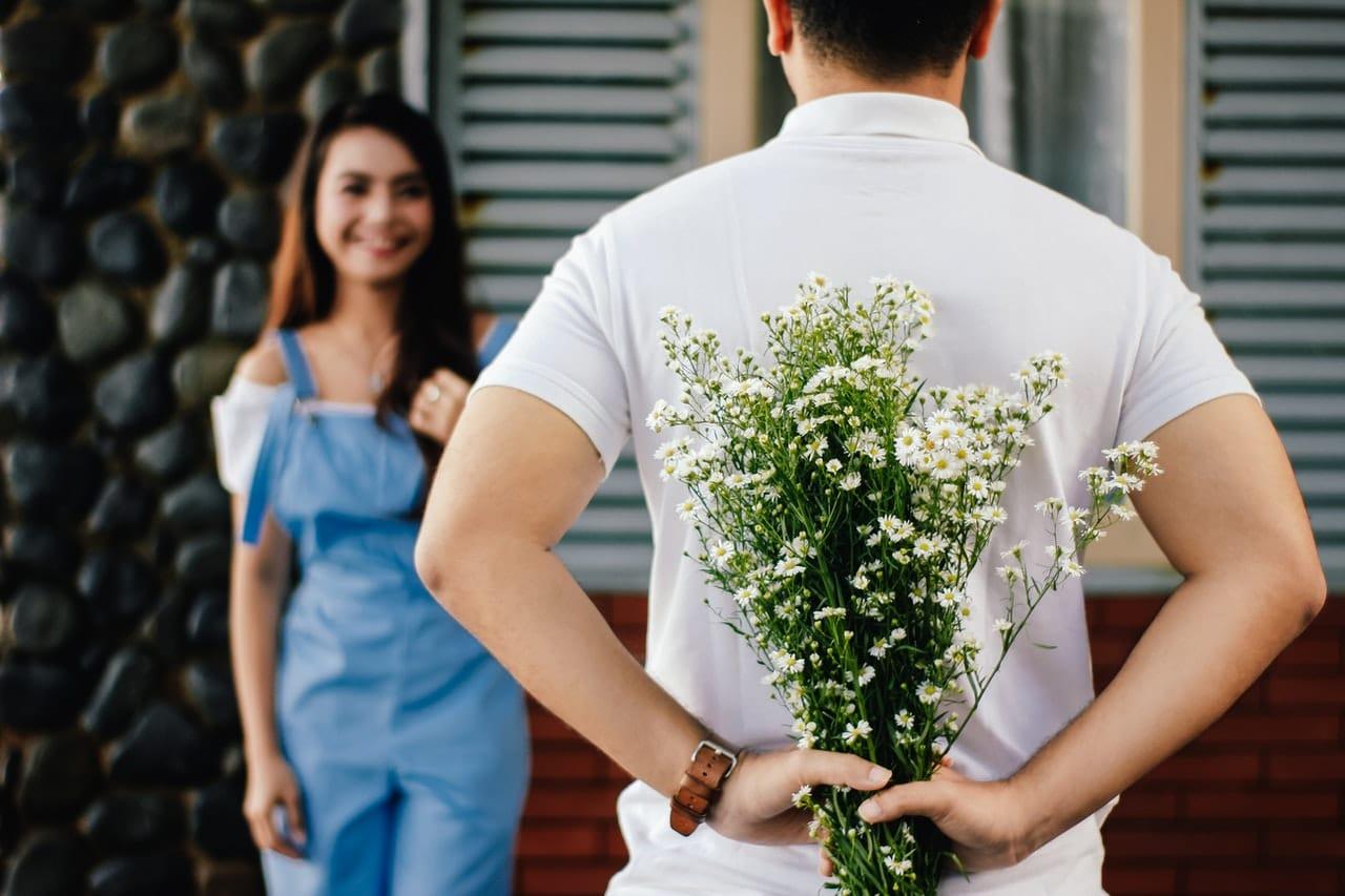 Mężczyzna wręczający kobiecie kwiaty na prezent