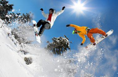 Młodzież skacze na deskach snowboardowych