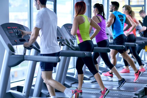 Ludzie biegnący na bieżniach