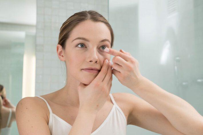 Kobieta zakładająca soczewki w łazience