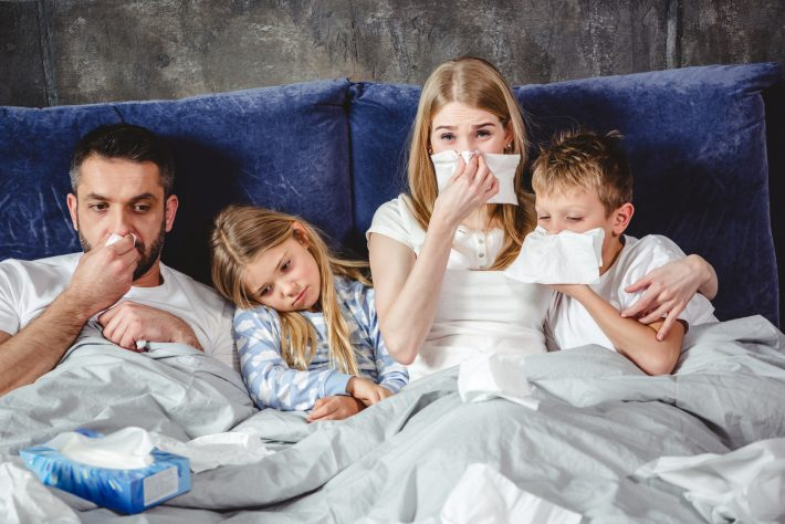 Przeziębiona rodzina leży w łóżku