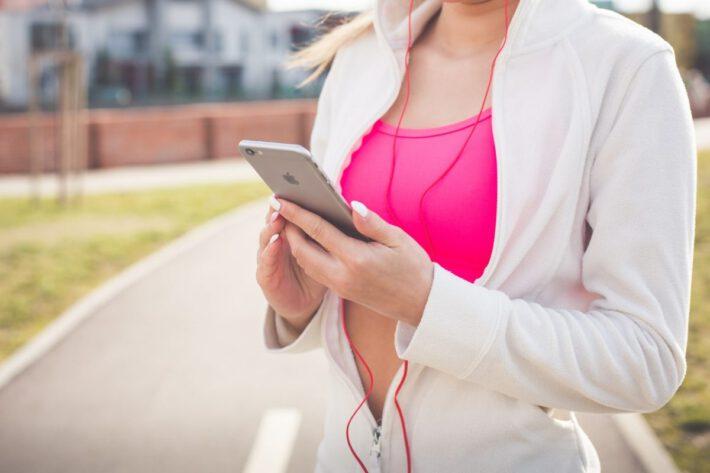 Kobieta korzystająca ze smatphone podczas uprawiania sportu