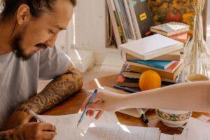 Mężczyzna podpisujący dokumenty wydziaraną w rękaw ręką