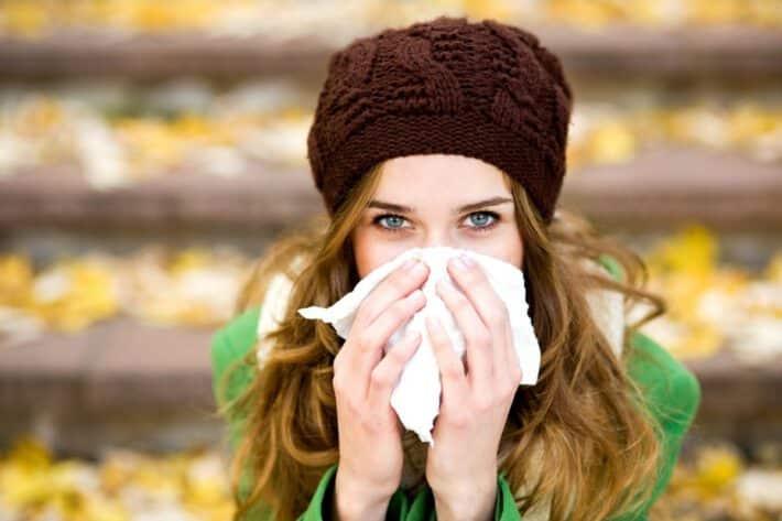 Przeziębiona kobieta smarka w chusteczkę