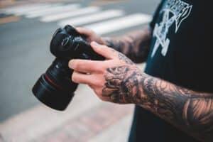 Tatuaż rękaw u mężczyzny trzymającego aparat w dłoniach