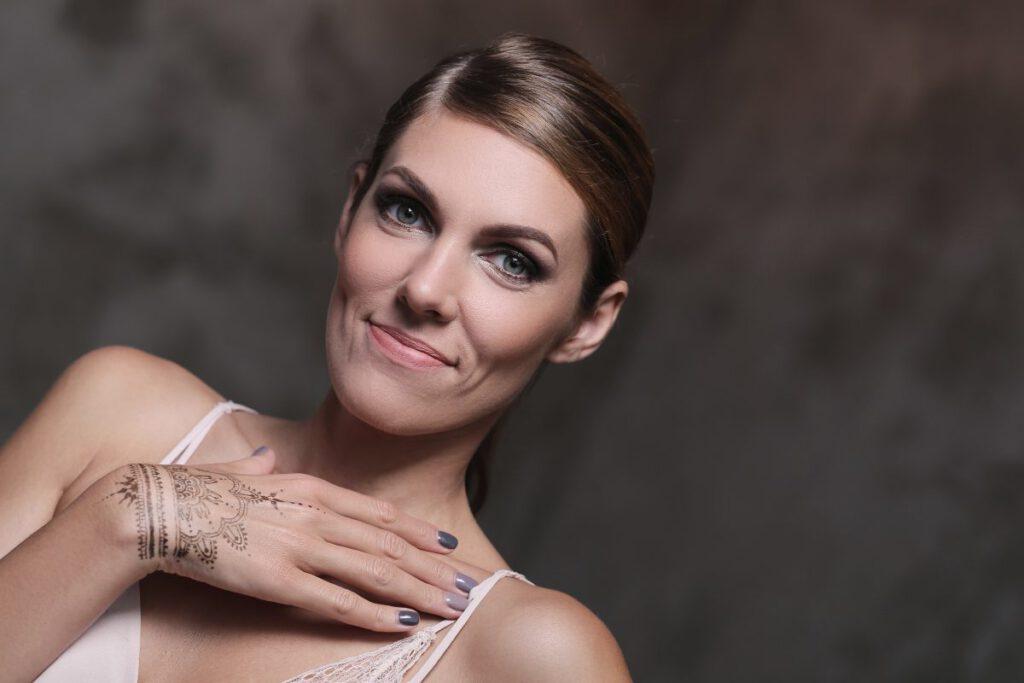 Uśmiechnięta młoda kobieta mająca na dłoni tatuaż
