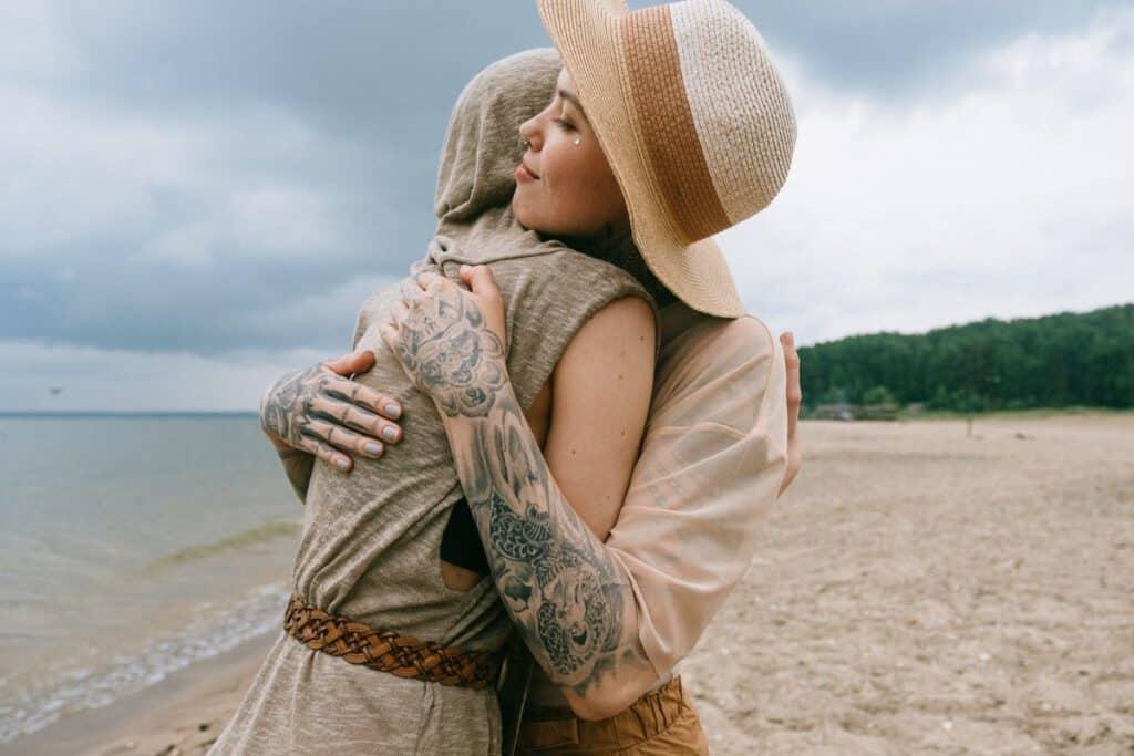 Kobieta z tatuażami na dłoni, która przytula swoja przyjaciółkę