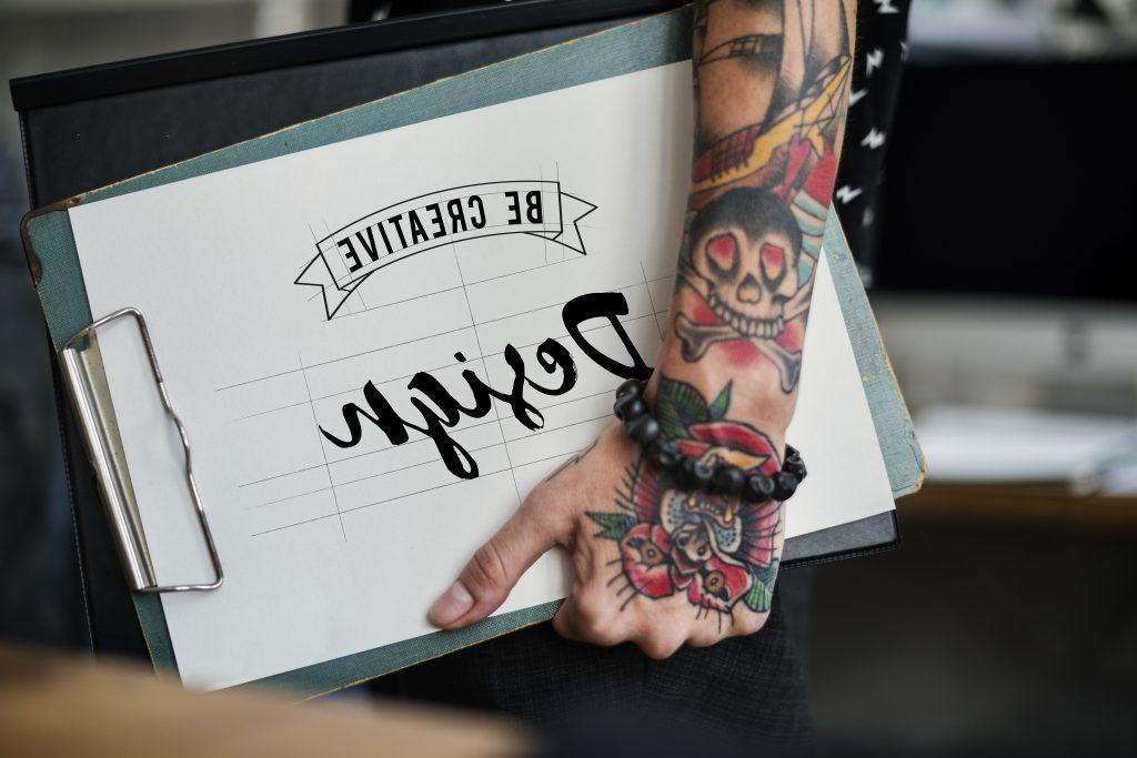 Kolorowy tatuaż na dłoni przypominający kwiat w kształcie twarzy zwierzęcia