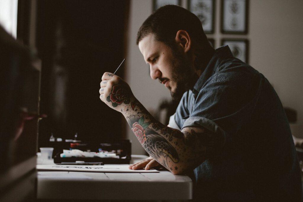 Mężczyzna z tatuażami na dłoni piszący coś na papierze