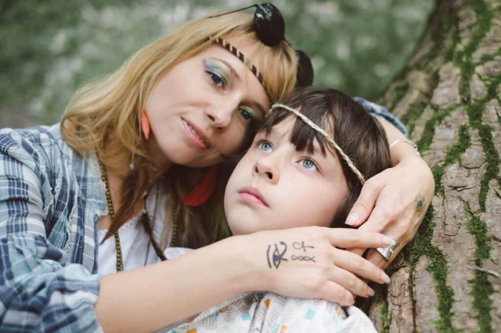 Mama z tatuażem na dłoni obejmująca swoje dziecko