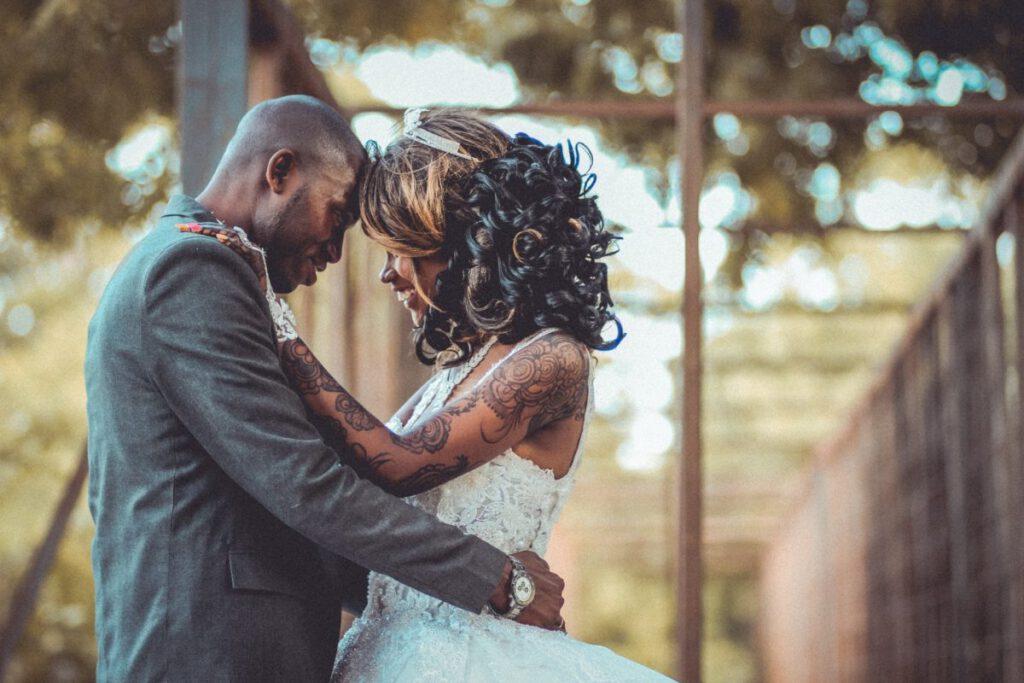 Panna młoda w białej sukni ślubnej z tatuażami na dłoniach w objęciach ukochanego