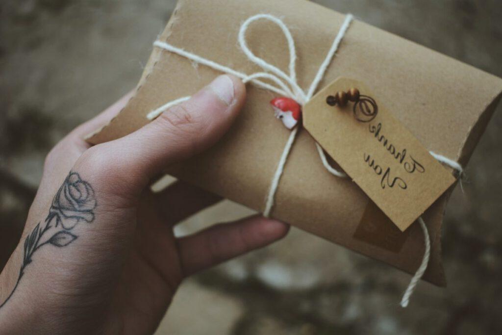 Kobieta z tatuażem na dłoni w kształcie różyczki trzymająca kopertę z podziękowaniami
