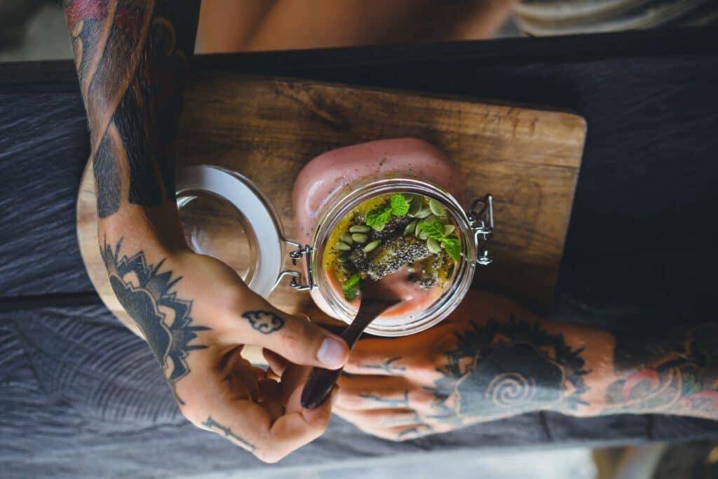 Mężczyzna z tatuażami na dłoniach jedzący drugie śniadanie
