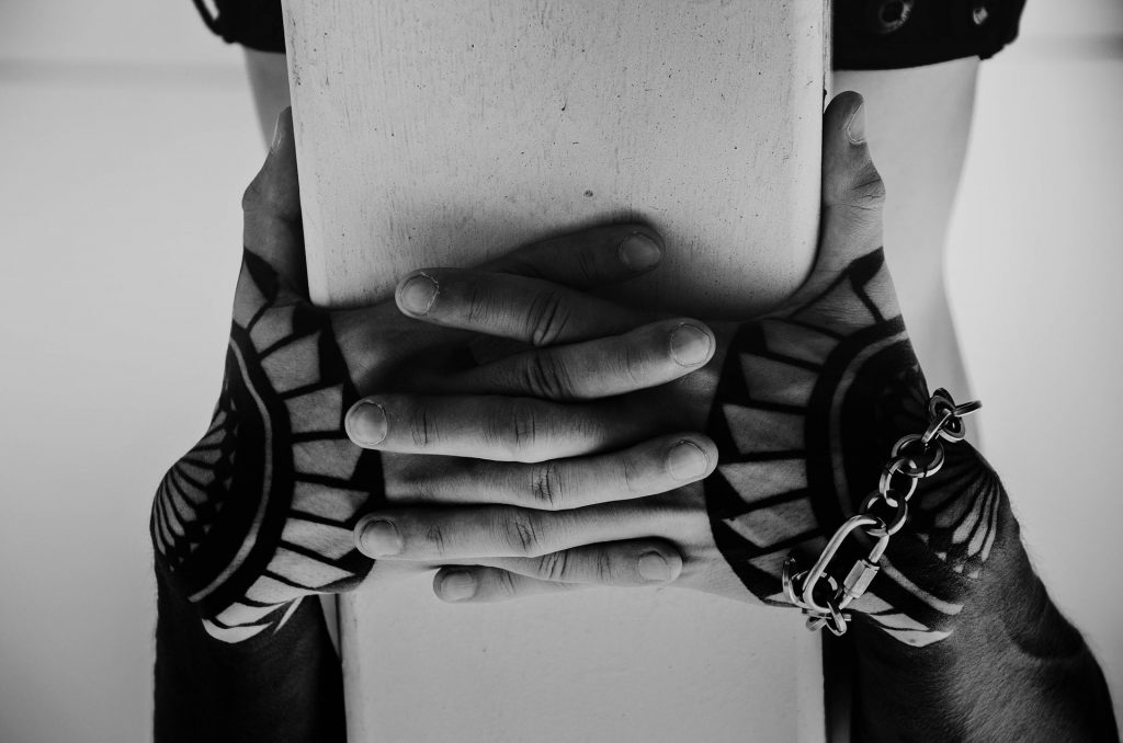 Czarno-białe zdjęcie przedstawiające męskie dłonie w tatuażach
