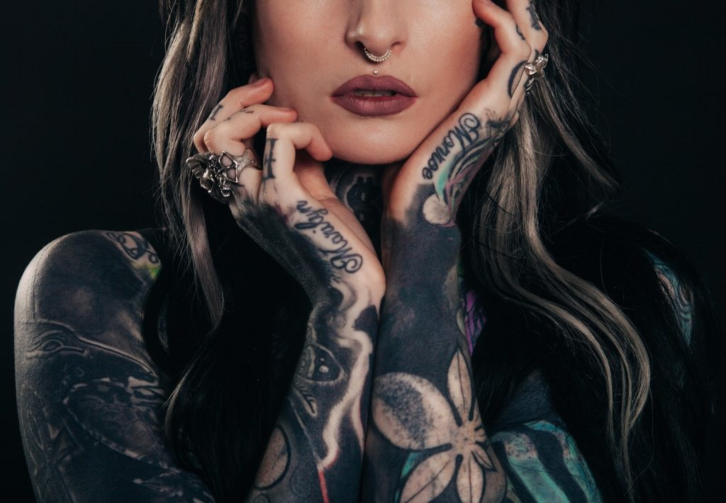 Młoda kobieta z tatuażami na dłoniach i rękach