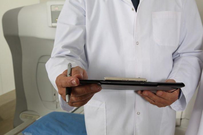 Lekarz trzymający w dłoni badania dotyczące martwicy kości udowej