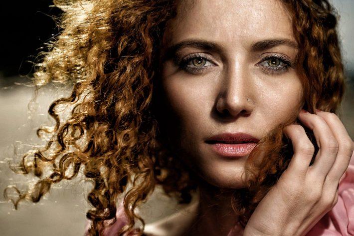 Kobieta z kręconymi włosami mająca makijaż na twarzy