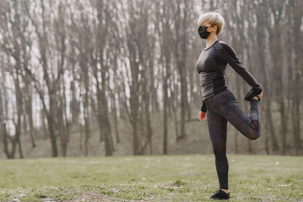 Kobieta ćwicząca z maską antysmogową na twarzy