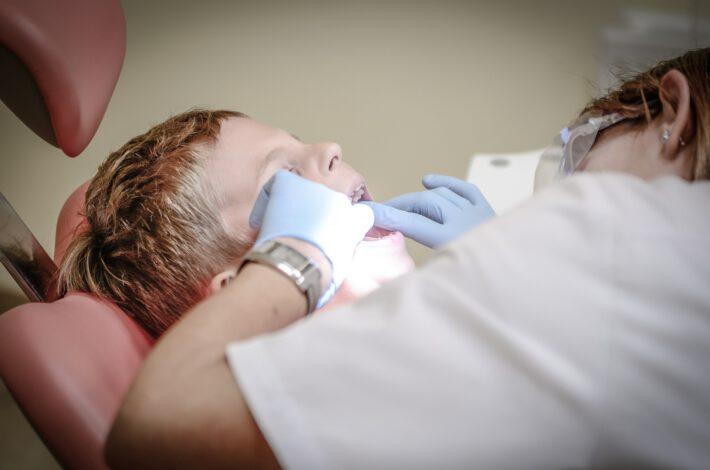 Dentystka sprawdza zęby chłopcu który siedzi na fotelu dentystycznym z otwartymi ustam