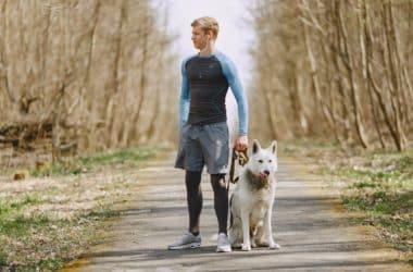 Mężczyzna biegający z psem po lesie