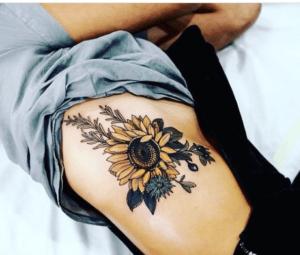 Damski tatuaż słonecznik na ciele kobiety leżącej na łóżku