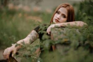Kobieta stojąca pośród roslin z damskim tauażem na ciele
