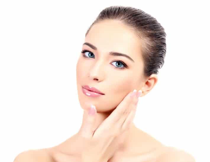 kobieta po karboksyterapi dotykająca swojej twarzy