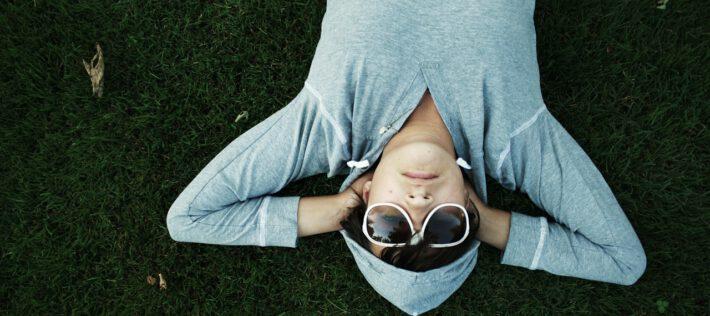 osoba leżąca na trawie w okularach przeciwsłonecznych
