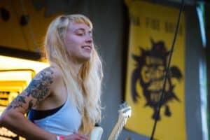 Tatuaż damski na ramieniu uśmiechniętej blondynki