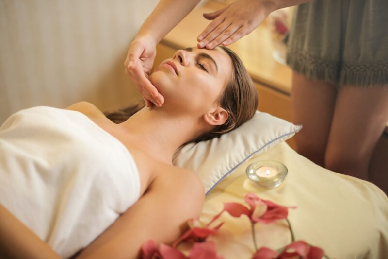 kobieta w trakcie masażu leczniczego, obok świeczka i kwiaty