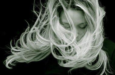 kobieta z długimi włosami której wiatr rozwiewa włosy
