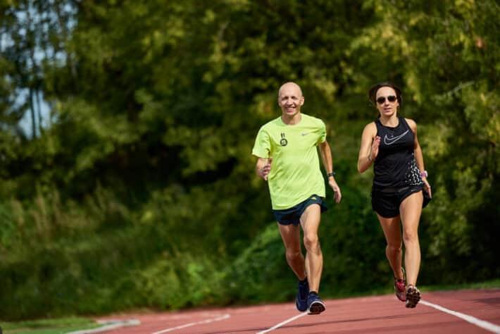 kobieta i mężczyzna biegną po tartanie