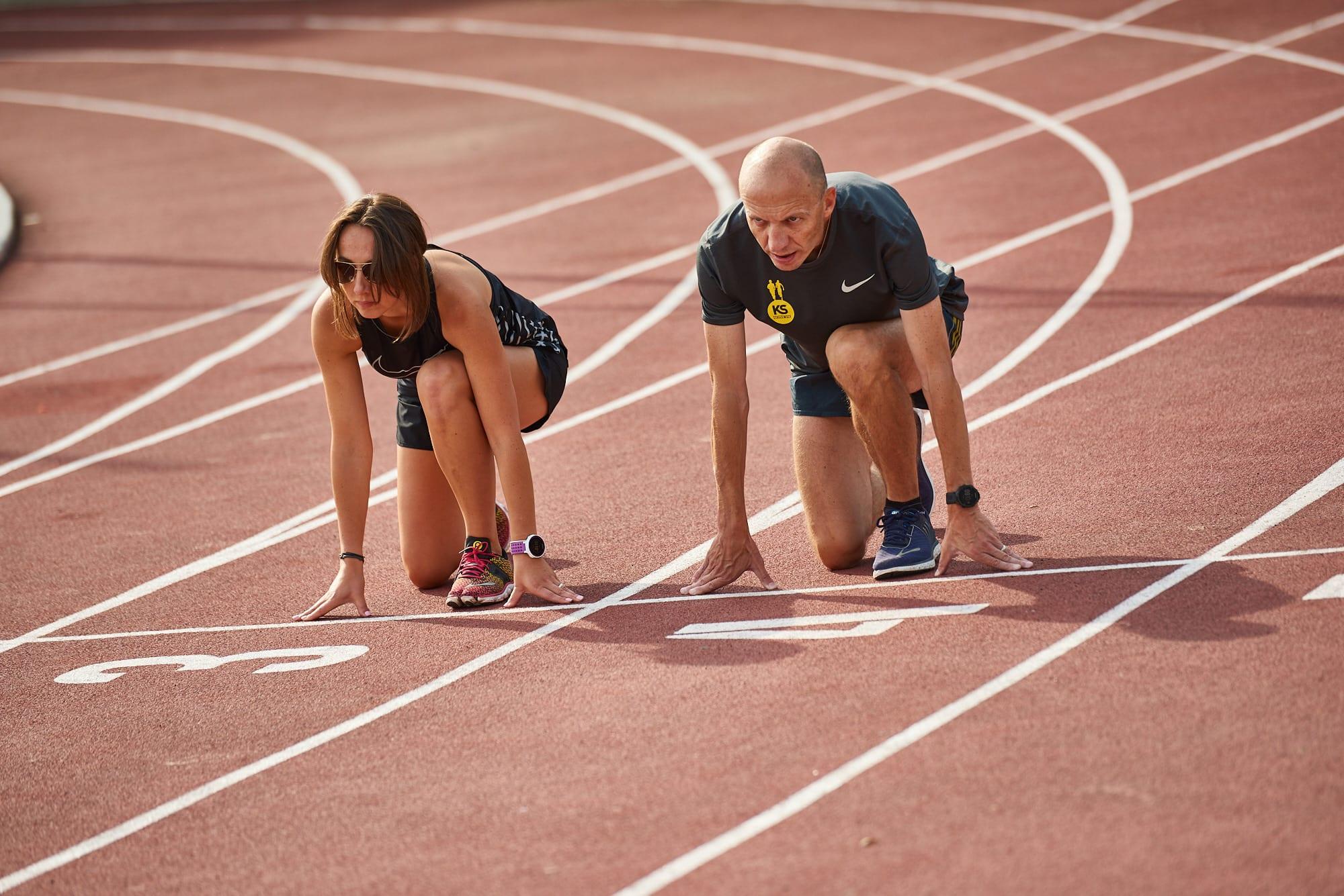 kobieta i mężczyzna przygotowują się do biegu na bieżni tartanowej