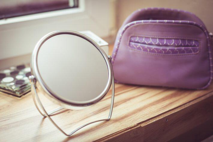 lustro stojąc na półce obok kosmetyczki
