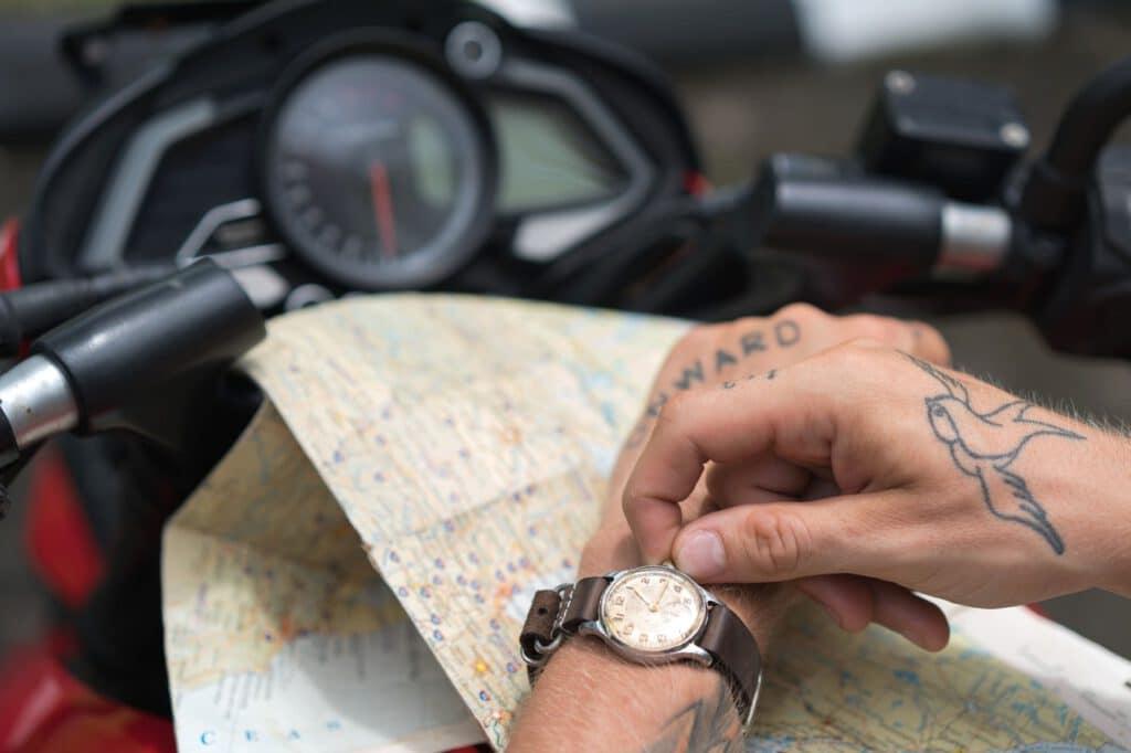 Wzór męskiego tatuażu na ręce faceta patrzacego na zegarek i trzymajacego na kolanach mapę