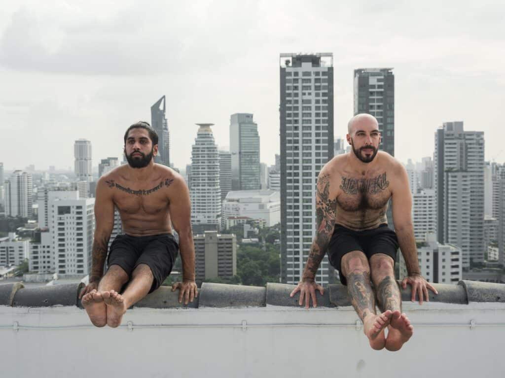 Mężczyźni w tatuażach podnoszący sie na barierce ku górze. W tle widoczne są wiezowce.
