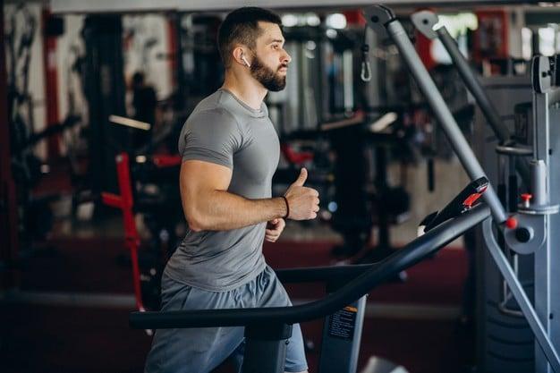 mężczyzna na siłowni trenujący na bieżni