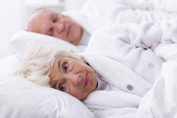 Bezsenność - leżąca w łóżku starsza kobieta, która nie może zasnąć.