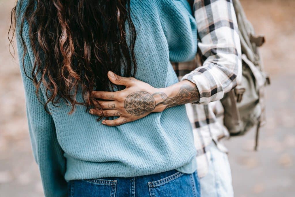 Mężczyzna z tatuażem na ręce obejmujący kobietę