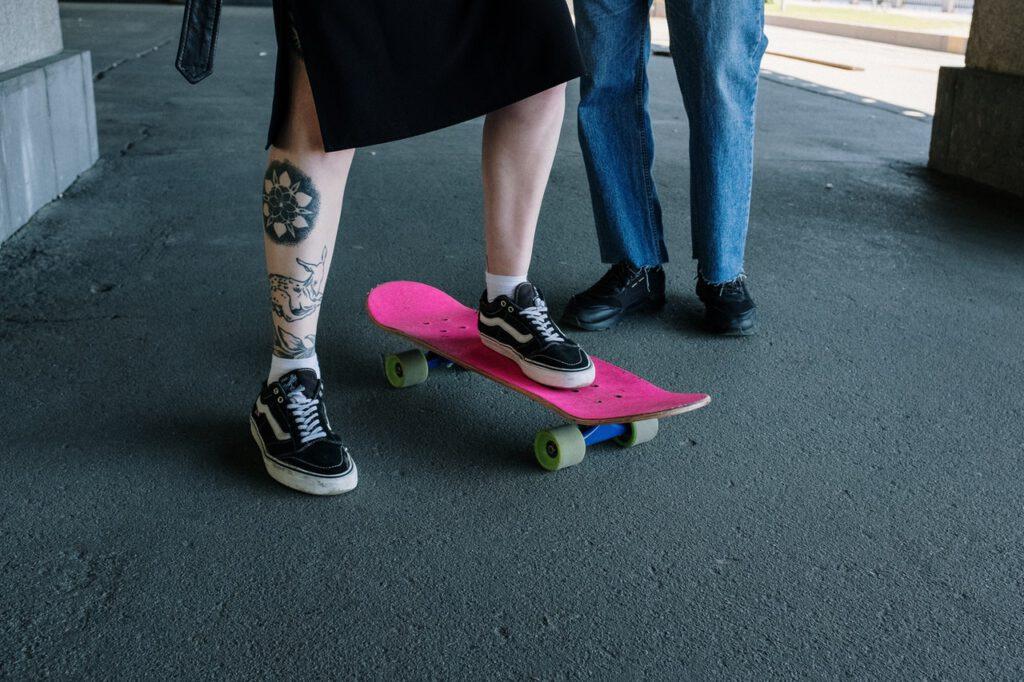 Tatuaż na łydce mężczyzny jadącego na deskorolce