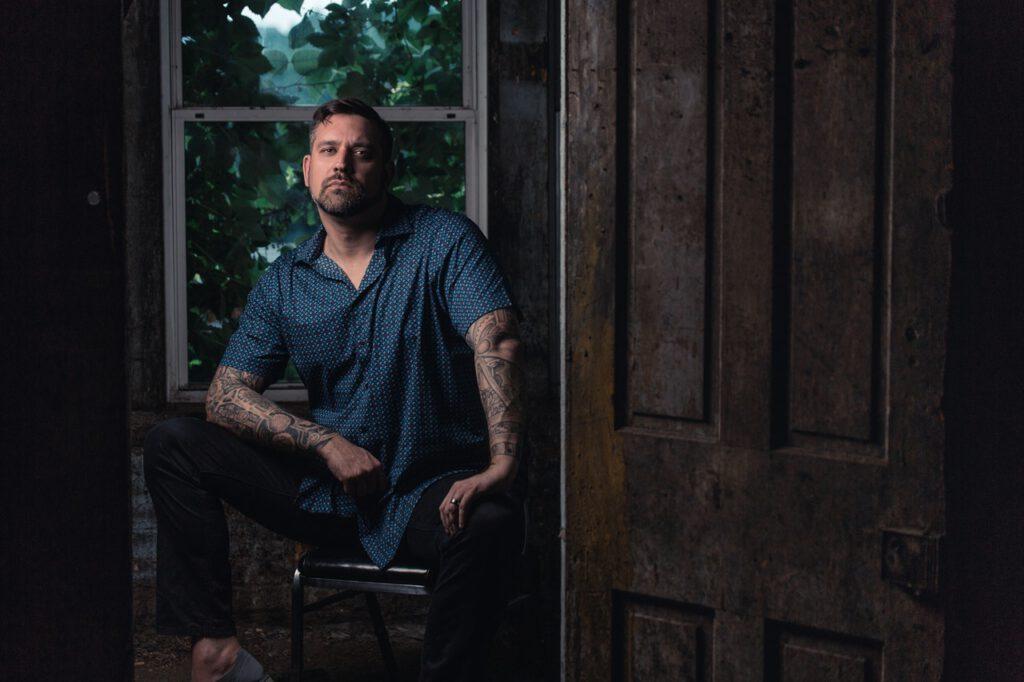 Siedzący mężczyzna z tatuażami na rękach