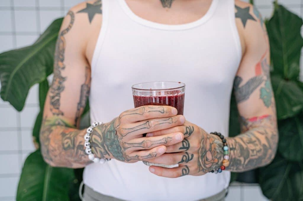 Mężczyzna z tatuażami na rękach, trzymający wypełnioną napojem szklankę