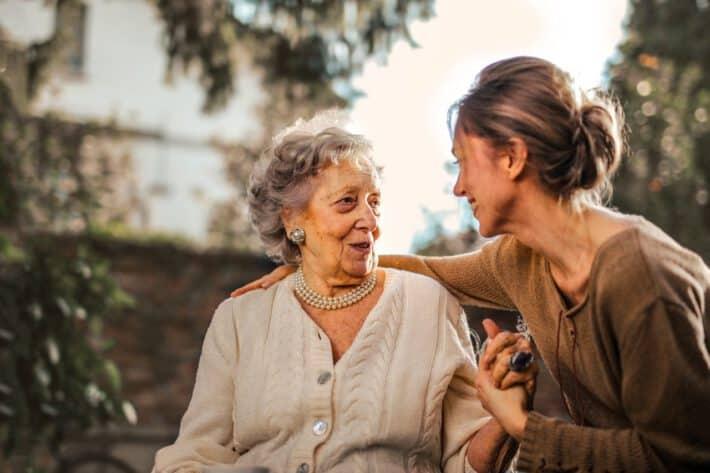 młoda kobieta trzyma za rękę starszą panią