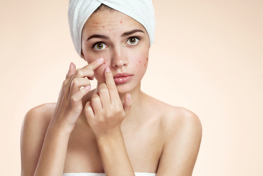 Kobieta sprawdza niedoskonałości swojej skóry