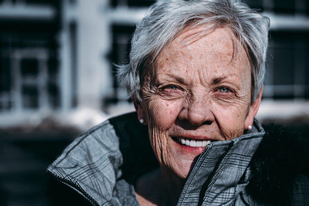 starsza kobieta uśmiechająca się, zastanawiająca się nad tym czy przeszczep brwi jest skuteczny