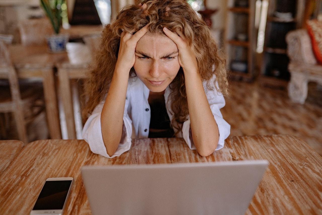 kobieta trzymająca się za głowę przed ekranem komputera