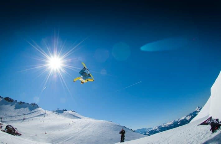 mężczyzna wykonujący obrót w powietrzu na snowboardzie