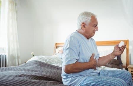 mężczyzna na łóżku z tabletkami w dłoni