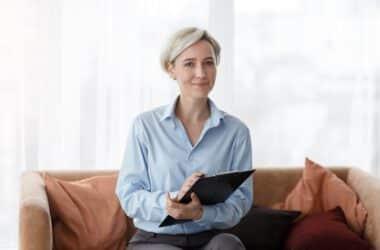 Psychologia sportu - pani psycholog z podkładką do notowania siedząca na kanapie.